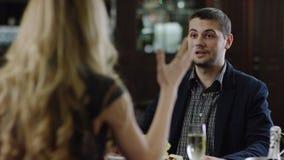 Muchacha que se encrespa que habla con el socio en el frente en restaurante metrajes