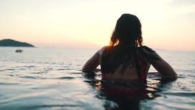 Muchacha que se enfría hacia fuera en la piscina en el fondo del océano en la puesta del sol almacen de metraje de vídeo