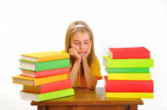 Muchacha que se enfurruña entre algunos libros Imagen de archivo libre de regalías