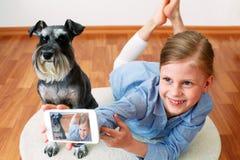 Muchacha que se fotografía y su perro Imagenes de archivo