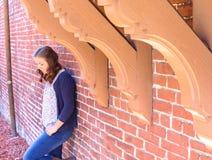 Muchacha que se inclina contra la pared de ladrillo roja Fotografía de archivo libre de regalías