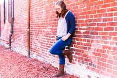 Muchacha que se inclina contra la pared de ladrillo roja Fotografía de archivo