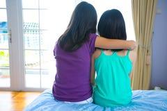 Muchacha que se inclina en el hombro de su hermana para el suppor foto de archivo