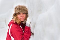 Muchacha que se inclina en la pared de la nieve Imagen de archivo libre de regalías