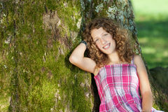 Muchacha que se inclina en tronco de árbol Imagen de archivo libre de regalías