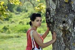 Muchacha que se inclina en un árbol Fotos de archivo libres de regalías
