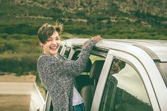 Muchacha que se inclina fuera de la puerta de una furgoneta imagen de archivo