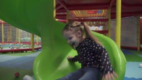 Muchacha que se mueve abajo en diapositiva en el centro del juego de niños metrajes