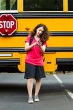 Muchacha que se niega a afrontar el autobús escolar mientras que manda un SMS en su teléfono Fotos de archivo libres de regalías