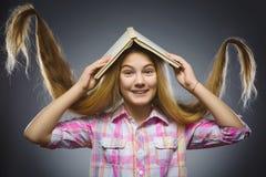 Muchacha que se pregunta con el libro por encima Retrato del primer de la camisa adolescente hermosa en fondo gris concepto de lo Fotos de archivo