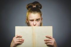 Muchacha que se pregunta con el libro Primer adolescente en fondo gris concepto de los estudios fotografía de archivo libre de regalías