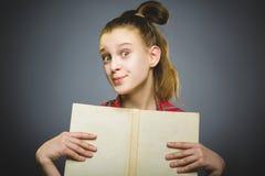 Muchacha que se pregunta con el libro Primer adolescente en fondo gris concepto de los estudios fotos de archivo libres de regalías