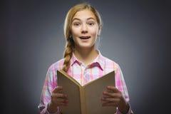 Muchacha que se pregunta con el libro Retrato del primer de adolescente hermoso en camisa sport en fondo gris concepto de los est Foto de archivo