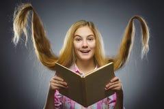 Muchacha que se pregunta con el libro Retrato del primer de adolescente hermoso en camisa sport en fondo gris concepto de los est Imagen de archivo