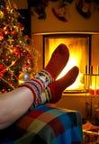 Muchacha que se reclina en sitio con la Navidad de la chimenea Foto de archivo libre de regalías