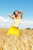 Muchacha que se reclina sobre campo asoleado del trigo Foto de archivo