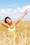 Muchacha que se reclina sobre campo asoleado del trigo Fotos de archivo