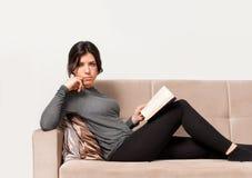 Muchacha que se reclina sobre el sofá Imagenes de archivo