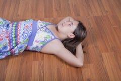 Muchacha que se reclina sobre el suelo de la sala de estar Imágenes de archivo libres de regalías