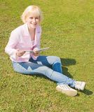Muchacha que se reclina sobre la hierba Imagen de archivo libre de regalías