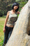 Muchacha que se relaja cerca de árbol Imagenes de archivo