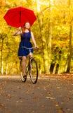 Muchacha que se relaja con el paraguas rojo de la bicicleta en parque del otoño Imagen de archivo