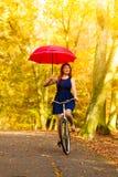 Muchacha que se relaja con el paraguas rojo de la bicicleta en parque del otoño Fotografía de archivo libre de regalías