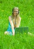 Muchacha que se relaja con la computadora portátil Fotos de archivo