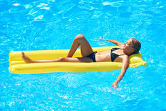 Muchacha que se relaja en el colchón de la natación en piscina imagenes de archivo