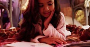 Muchacha que se relaja en el colchón y el libro de lectura almacen de metraje de vídeo