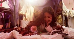 Muchacha que se relaja en el colchón y el libro de lectura almacen de video