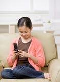 Muchacha que se relaja en el sofá y el envío de mensajes de texto Imagen de archivo