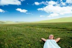 Muchacha que se relaja en hierba Fotos de archivo libres de regalías