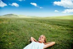 Muchacha que se relaja en hierba Imagen de archivo