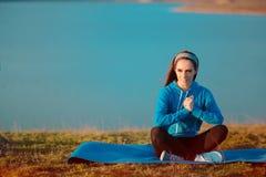 Muchacha que se relaja en la estera de la yoga en naturaleza Fotografía de archivo libre de regalías