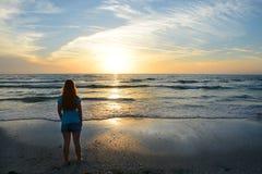 Muchacha que se relaja en la playa en la puesta del sol Fotos de archivo
