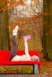 Muchacha que se relaja en libro de lectura del parque del otoño Fotografía de archivo
