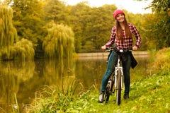 Muchacha que se relaja en parque otoñal con la bicicleta Foto de archivo libre de regalías