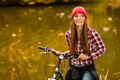 Muchacha que se relaja en parque otoñal con la bicicleta Fotografía de archivo