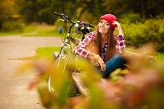 Muchacha que se relaja en parque otoñal con la bicicleta Foto de archivo