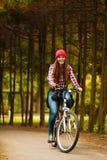 Muchacha que se relaja en parque otoñal con la bicicleta Imagenes de archivo