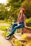 Muchacha que se relaja en parque otoñal con la bicicleta Fotos de archivo