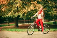 Muchacha que se relaja en parque otoñal con la bicicleta Imágenes de archivo libres de regalías