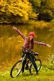 Muchacha que se relaja en parque otoñal con la bicicleta Fotografía de archivo libre de regalías
