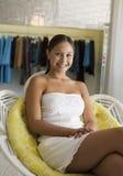 Muchacha que se relaja en silla en retrato del boutique de la ropa Fotografía de archivo libre de regalías