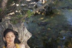 Muchacha que se relaja en tronco de árbol por la corriente Fotografía de archivo