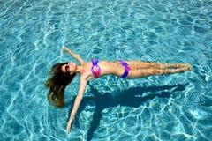 muchacha que se relaja en una piscina Imagen de archivo