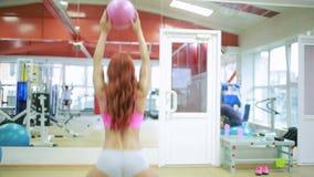 Muchacha que se resuelve con la bola de medicina en gimnasio metrajes