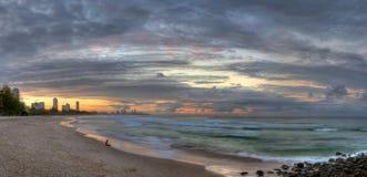 Muchacha que se sienta adelante en la playa en la puesta del sol foto de archivo libre de regalías
