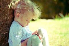 Muchacha que se sienta al lado del árbol Fotografía de archivo